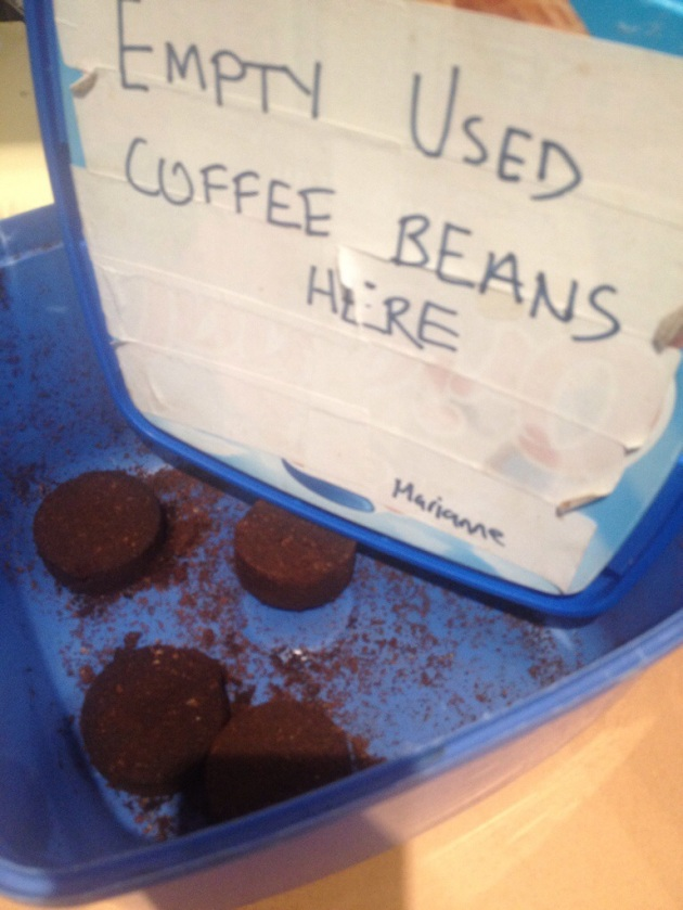 spent coffee ground pucks in container
